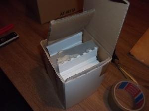 A lezárást is úgy kell megoldani, hogy az orrvédő ne mozdulhasson el. Ezzel készen is van, leragasztottuk, vastag csomagolópapírba burkoltuk az egész dobozt, és újra leragasztottuk. Irány a posta.
